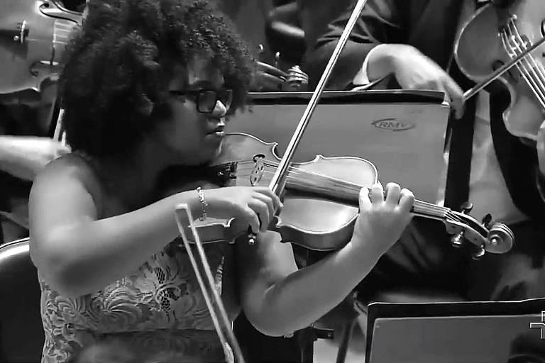 Moça negra toca viola com outros músicos ao fundo