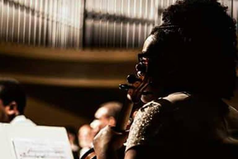 Moça negra olha partitura e segura viola; ao fundo, tubos de um órgão