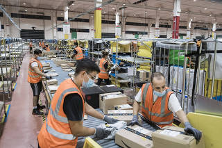 Amazon employees process packages at a delivery station in Arzano, Italy on Sept. 18, 2020. (Gianni Cipriano/The New York Times)