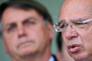 Brazil's Economy Minister Paulo Guedes speaks next Brazil's President Jair Bolsonaro during a press statement at the Alvorada Palace in Brasilia