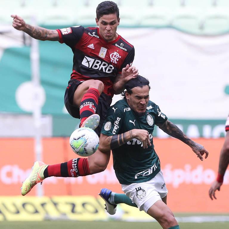 O zagueiro palmeirense Gustavo Gómez disputa bola com o atacante rubro-negro Pedro no duelo de domingo (27), que quase foi adiado