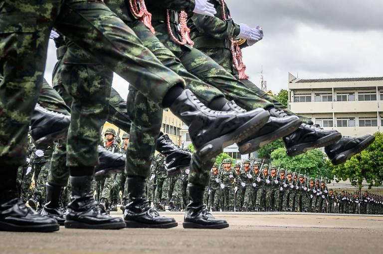 Quatro soldados retratados da cintura para baixo erguem a perna esquerda em movimento sincronizado; ao fundo, dezenas de soldados