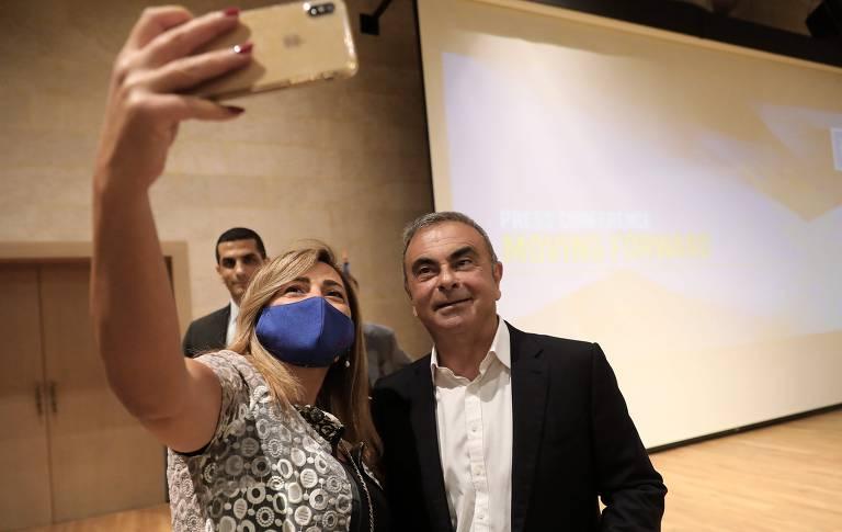 Ghosn, sem máscara, ao lado de uma mulher, que  usa a proteção e ergue o celular com a mão direita para tirar selfie com o ex-executivo