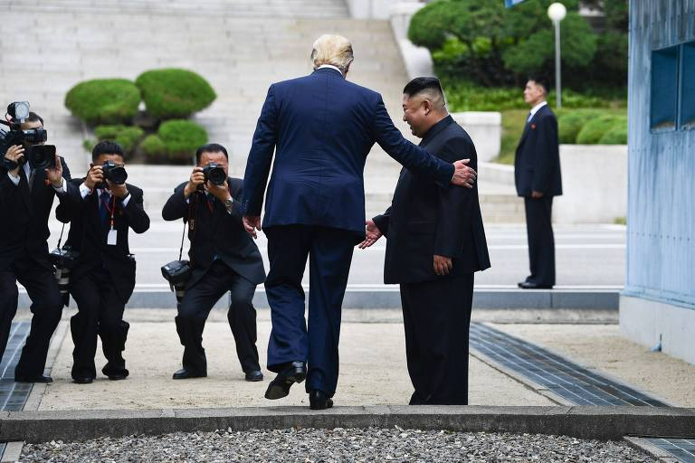 O presidente dos EUA, Donald Trump, de costas, entra no lado norte da zona desmilitarizada entre as Coreias, acompanhado do ditador Kim Jong Un