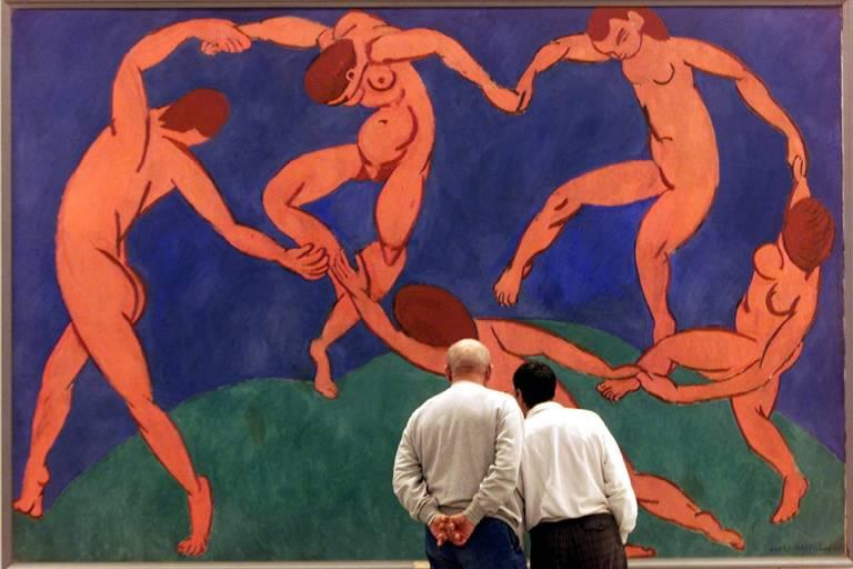 Homens olham pintura que retrata dança de mulheres