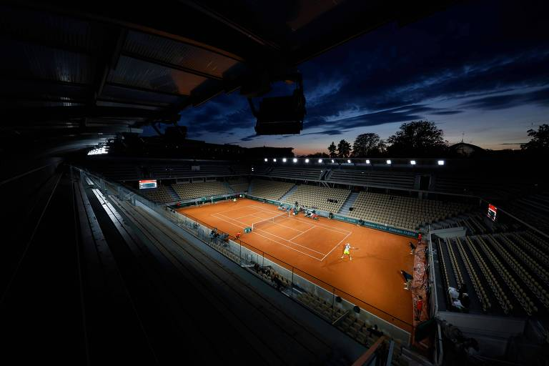Uma das quadras do complexo de Roland Garros iluminada durante partida noturna do torneio