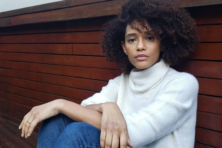 A atriz Tais Araujo veste uma blusa branca de gola alta e calça jeans. Ela está sentada com os braços apoiados nos joelhos e olha para a câmera.