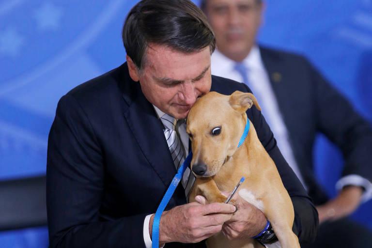 O presidente Jair Bolsonaro segura o cachorro Sansão em cerimônia no Palácio do Planalto