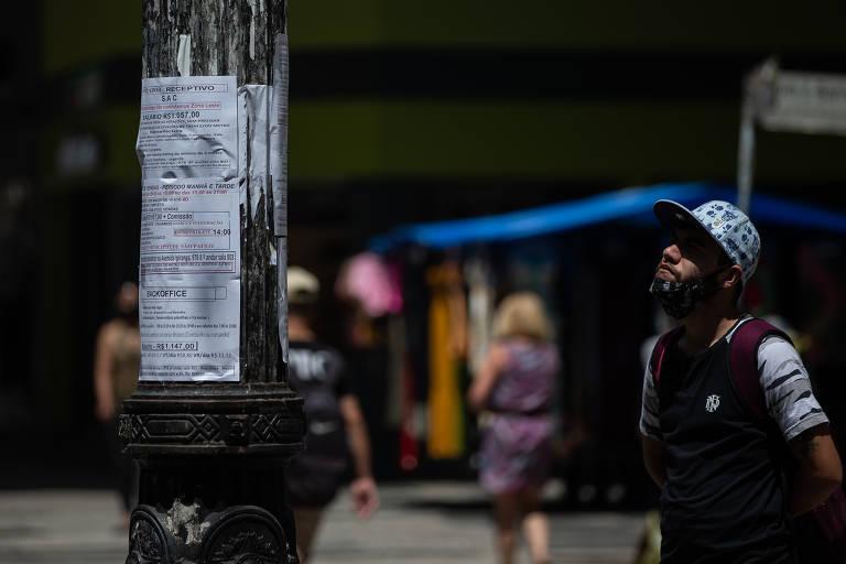 Jovem olha vagas de emprego em poste com anúncios