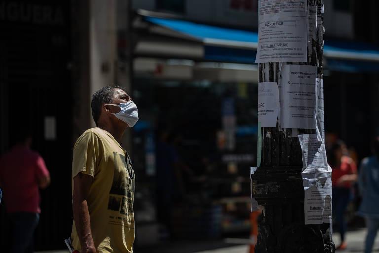 Homem olha para anúncios de vagas colados em postes de luz, na Barão de Itapetininga, no centro de São Paulo
