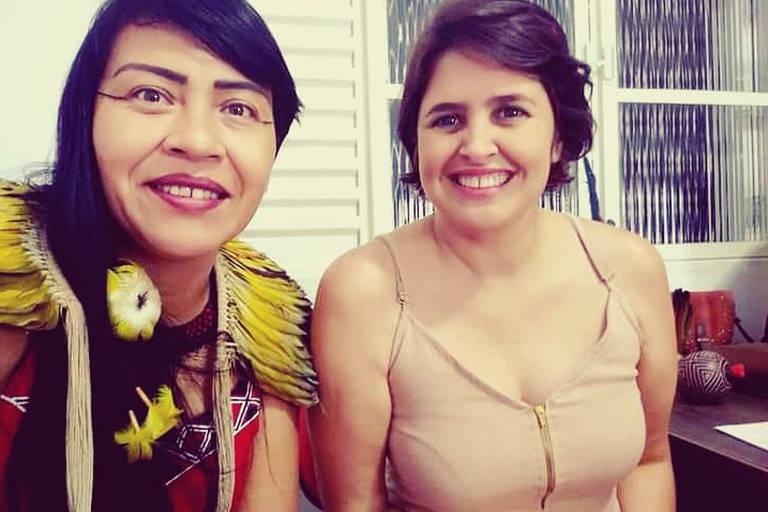 Uma mulher com pintura e adornos indígenas, de cabelos longos, está ao lado de outra mulher de cabelo curto e blusa clara