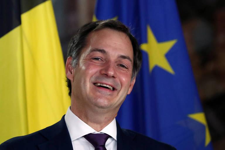 Homem de gravata preta, camisa branca e paletó preto sorri com bandeira amarela preta e vermelha e bandeira azul com estrelas amarelas ao fundo