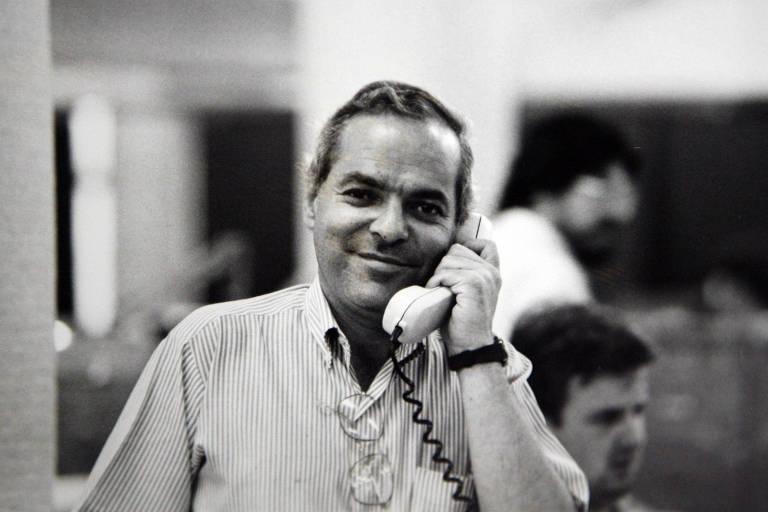 retrato em preto e branco do repórter João Batista Natali sorrindo e falando ao telefone na redação do jornal - um escritório grande repleto de mesas compridas e computadores