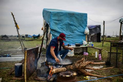 A man cooks outside a tent set up in land occupied by homeless people outside Guernica, in the province of Buenos Aires, south of the Argentine capital, on August 28, 2020 amid rising poverty in an economic crisis exacerbated by the COVID-19 novel coronavirus pandemic. - Outdoors or under makeshift tents, about 2,500 people have been defying justice, and COVID-19, for more than a month, when they occupied empty lots in Buenos Aires Province, the most populous of the country and where the pandemic is hitting the hardest. Scattered in over 100 hectares of vacant land, children run around and adults talk, while the police guards the area. Prevention measures against the novel coronavirus barely exist here. (Photo by Ronaldo SCHEMIDT / AFP) ORG XMIT: RSA1474