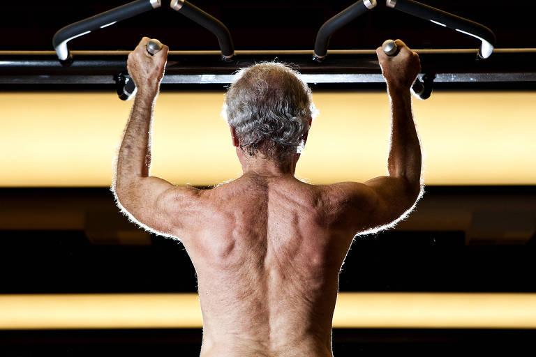 homem de cabelos brancos, de costas e sem camisa, faz musculação levantando peso com os dois braços