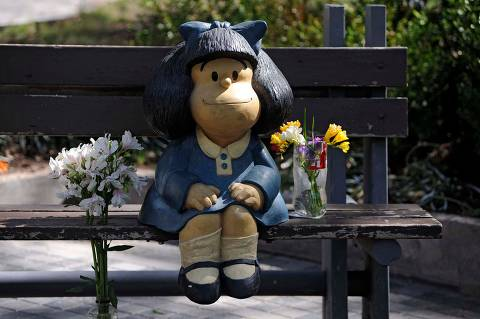 TOPSHOT - Flowers are seen by a statue depicting Mafalda, a comic strip character created by Argentinian cartoonist Joaquin Salvador Lavado, known as Quino, in Mendoza, Argentina, on September 30, 2020, on the day of his death. - Quino passed away Wednesday at 88, his editor confirmed. (Photo by Andres LARROVERE / AFP)