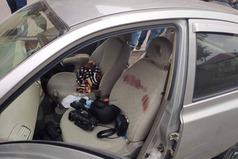 Câmera de equipe armênia fica sobre banco manchado de sangue em carro atingido por estilhaços, em Martuni