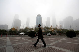 FILE PHOTO: Man wearing a mask walks in the central business district on a polluted day after a yellow alert was issued for smog, in Beijing
