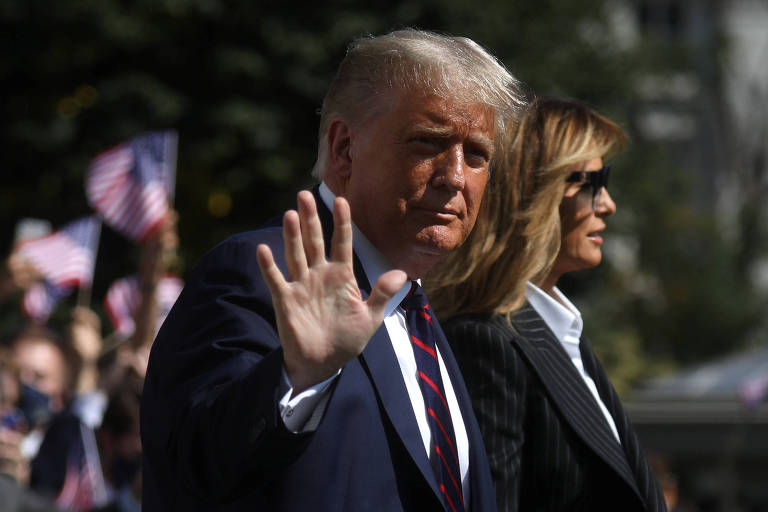 O presidente dos EUA, Donald Trump, acena antes de partir de Washington ao lado da primeira-dama Melania