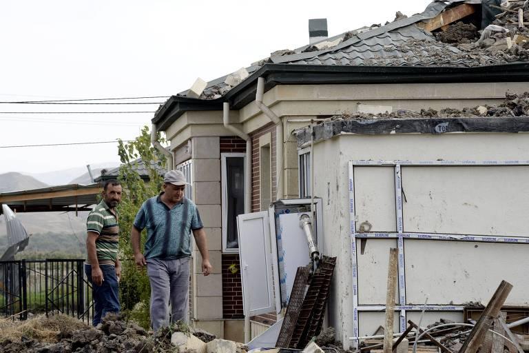 Moradores em casa atingida por artilharia azeri em Djojugh Marjanli, cidade controlada por armênios no Azerbaijão