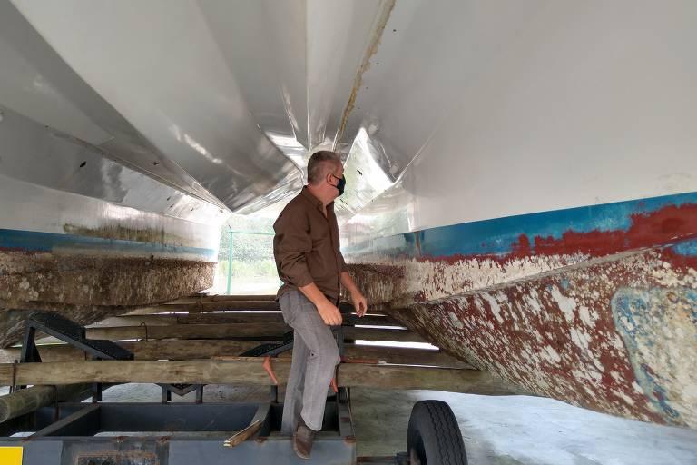 homem observa cascos de  metal de uma embarcação com sinais de deterioração