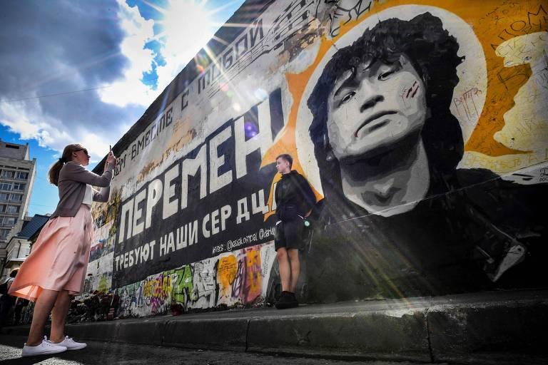 Turistas tiram foto em frente à imagem de Viktor Tsoi em um muro de Moscou