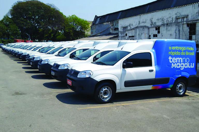 Furgões Fiorino da Movida com personalização do Magalu enfileirados em estacionamento