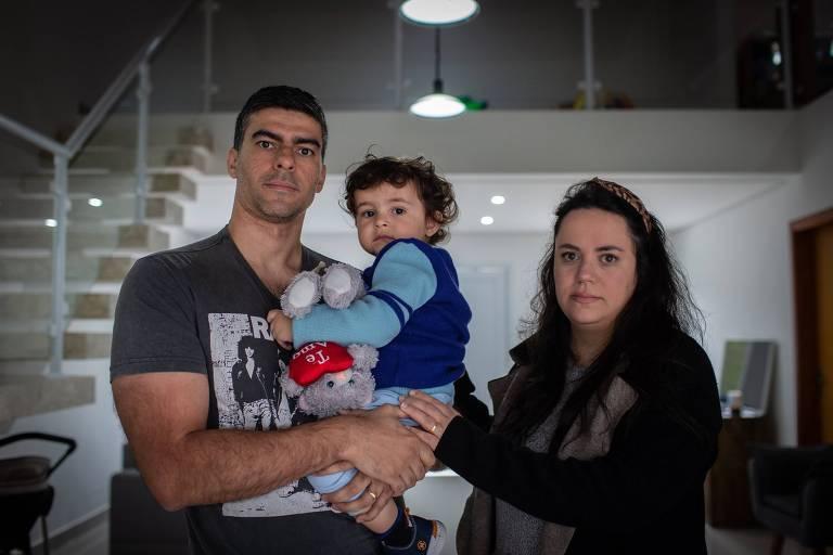 Miguel, de um ano e oito meses, com sua mãe, Caroline Cunha, e seu pai, Adriano Jorge de Oliveira, é uma das crianças que tiveram Sim-P no país