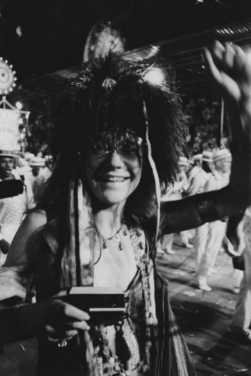 Mulher com óculos e adereços no cabelo sorri e levanta mão esquerda