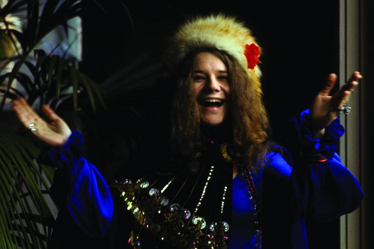 Mulher com chapéu peludo dá risada
