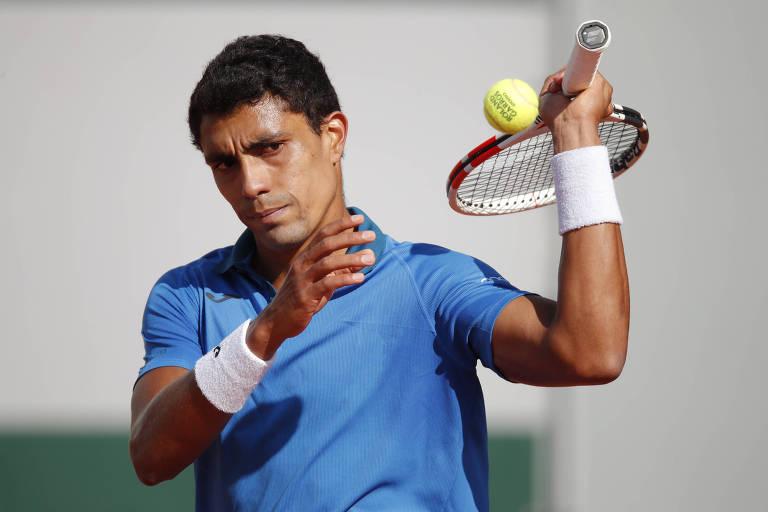 Tenista de camiseta azul bate na bola com a raquete