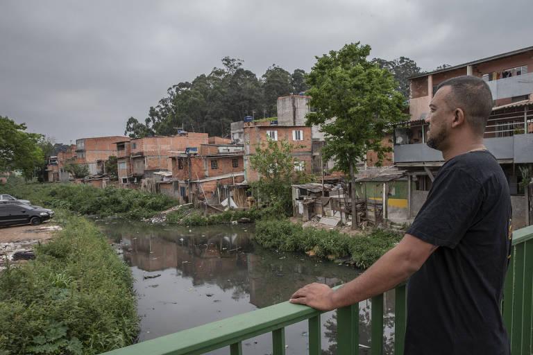 Um homem olhando para um rio poluído cercado de casas inacabadas