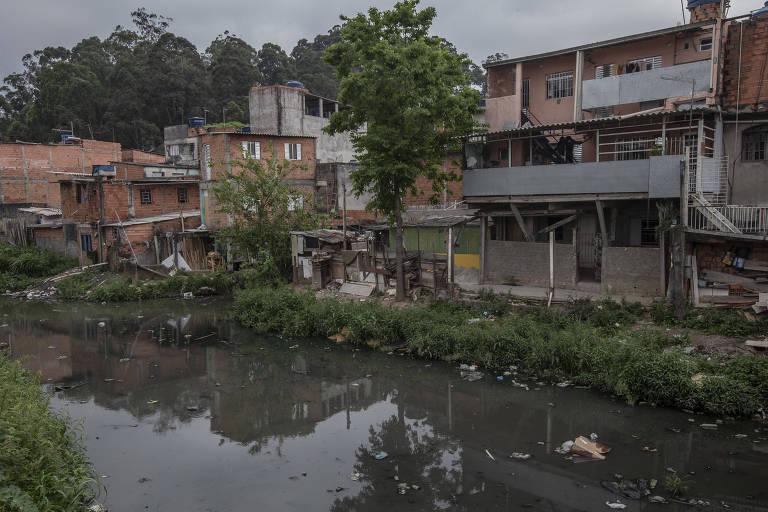 Rio poluido com casas no entorno