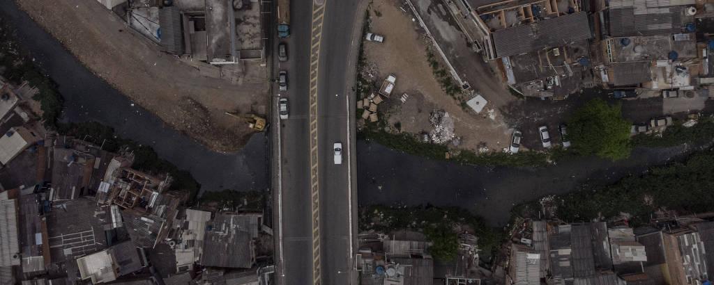 Vista aérea de um córrego poluido por baixo de uma avenida. Ao lado do córrego, várias casas