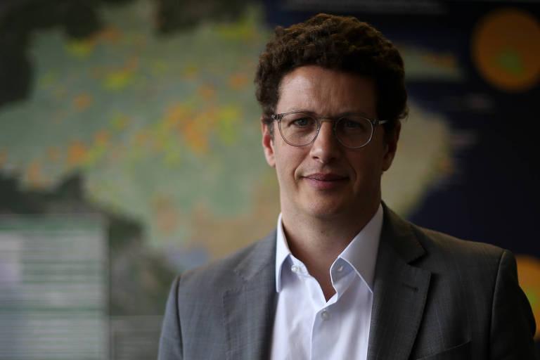 De blazer cinza e camisa branca, Salles, um homem branco de meia idade, cabelo crespo e óculo, encara a câmara; por trás dele, enxerga-se um mapa do Brasil
