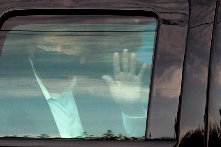 O presidente Donald Trump acena de dentro de carro a apoiadores nas proximidades do hospital Walter Reed, onde está internado