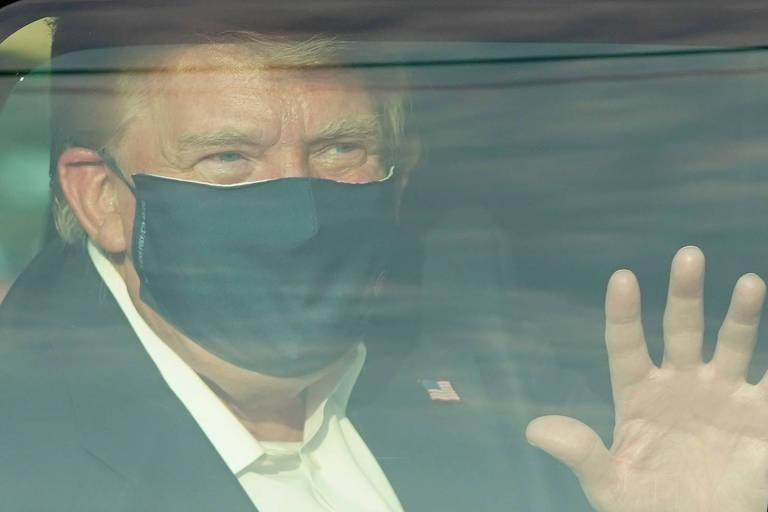 O presidente Donald Trump acena de dentro de carro a apoiadores nas proximidades do hospital Walter Reed