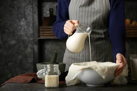 Woman making healthy rice milk in kitchen
