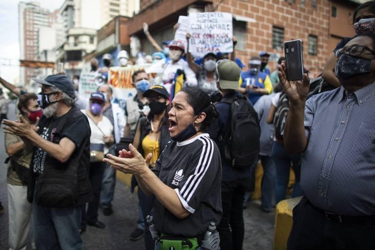 Mulher tira máscara para protestar durante ato por melhores salários e condições de trabalho para professores em Caracas, na Venezuela