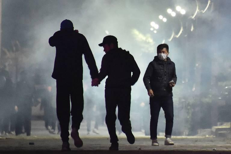 Manifestantes fogem de gás lacrimogêneo durante confronto com a polícia em Bishkek