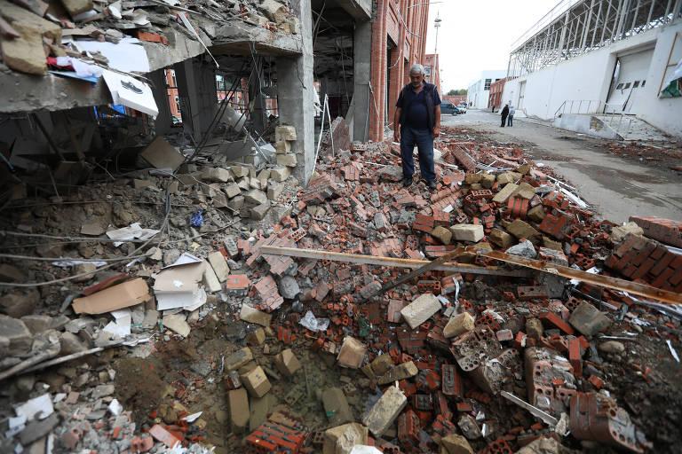Homem examina prédio atingido por artilharia de separatistas armênios em Ganja, no Azerbaijão