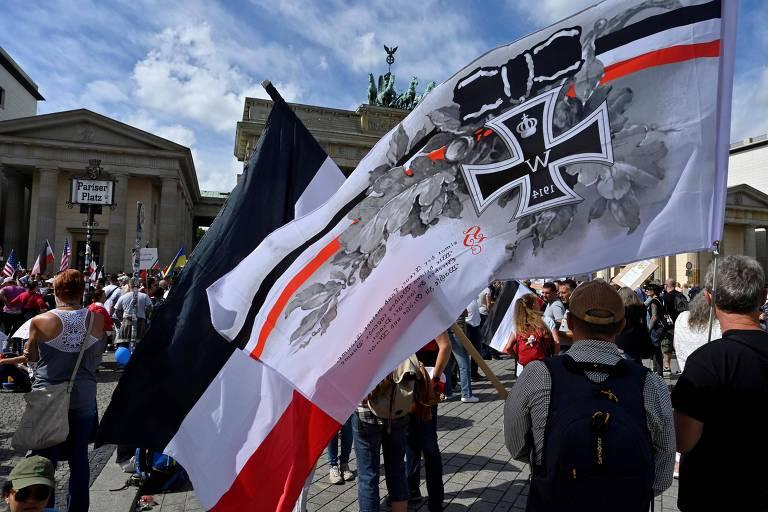 manifestante com bandeira brnaca, preta e vermelha