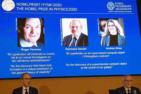 David Haviland (L), member of the Nobel Committee for Physics, and Goran K Hansson, Secretary General of the Academy of Sciences, sit in front of a screen displaying the winners of the 2020 Nobel Prize in Physics (L-R) Briton Roger Penrose, Reinhard Genzel of Germany  and Andrea Ghez of the US, during a press conference at the Royal Swedish Academy of Sciences, in Stockholm, on October 6, 2020. - Roger Penrose of Britain, Reinhard Genzel of Germany and Andrea Ghez of the US won the Nobel Physics Prize on Tuesday for their research into black holes, the Nobel jury said. (Photo by Fredrik SANDBERG / TT NEWS AGENCY / AFP) / Sweden OUT