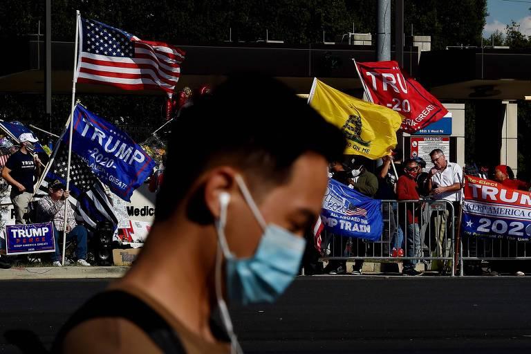 Homem de máscara passa em frente a apoiadores de Donald Trump em frente ao hospital Walter Reed, onde o presidente ficou internado