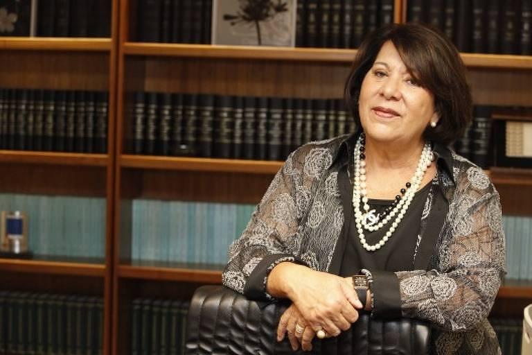 Ex-ministra do STJ Eliana Calmon com uma blusa preta e estampada e colar de pérola segura suas mãos e as apoia em uma cadeira de couro. De fundo há uma estante de livros.