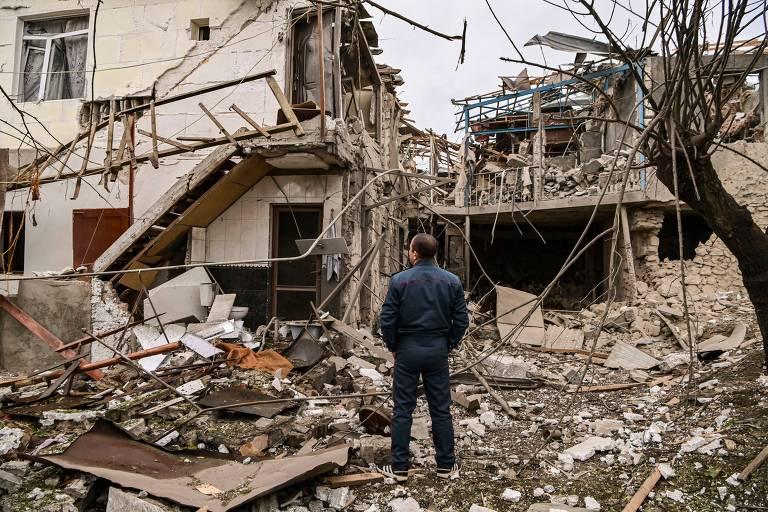 Policial olha casa destruída em bombardeio na capital de Nagorno-Karabakh, Stepanakert