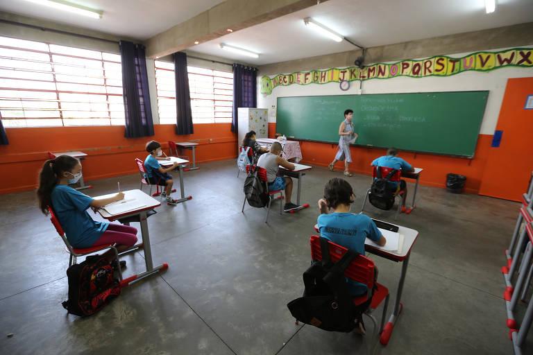 Alunos sentados distantes uns dos outros em sala de aula