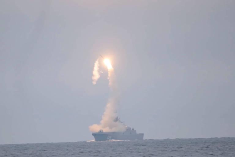 Míssil deixa rastro de fumaça e fogo depois de ser lançado de um navio em um mar cinzento