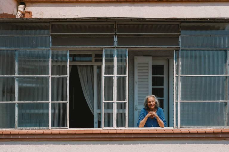 mulher de cabelos brancos veste azul e está com os braços apoiados no parapeito de uma grande janela de vidro fosco. ela olha para a câmera e sorri.