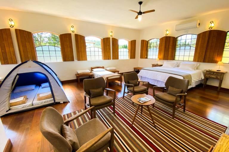 Quarto com janelas de madeira, barraca e tapete